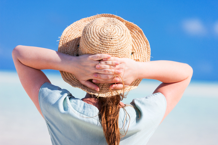 woman back view: Back view of a young beautiful woman in straw hat at tropical beach Stock Photo