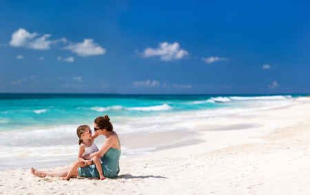 Mother and daughter enjoying beach vacation photo