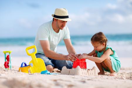 Fader och dotter på stranden byggnad sand slott Stockfoto