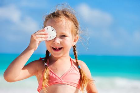 sand dollar: Ni�a adorable en la playa tomados de la arena d�lar