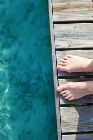 Woman legs close up at wooden jetty by the sea photo