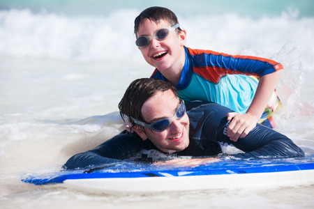 Father and son surfing on boogie boards photo