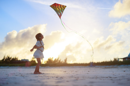 kite flying: Little girl flying a kite on beach at sunset Stock Photo
