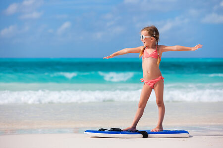 Little girl practicing surfing position at beach
