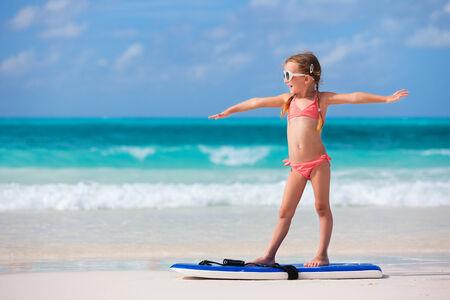 Petite fille à pratiquer la position de surf à la plage Banque d'images - 27613392