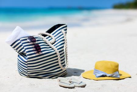 Chapeau de paille, sac, lunettes de soleil et des tongs sur une plage tropicale Banque d'images