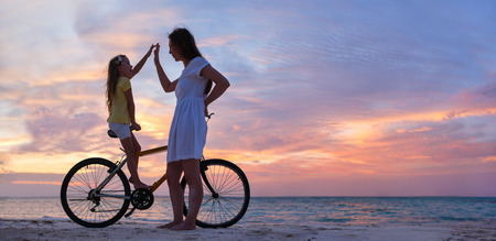 Mother and daughter with bike on a beach at sunset photo