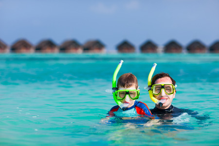 Happy father and son snorkeling in a tropical ocean  photo