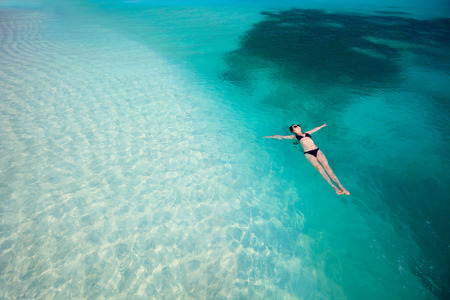 Vacker kvinna som flyter i turkos tropiskt vatten