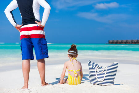 Back view of father and daughter at tropical beach photo