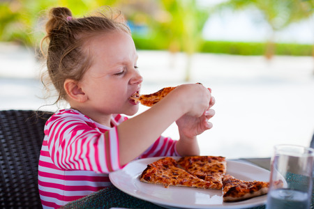 Adorable little girl eating pizza for lunch photo