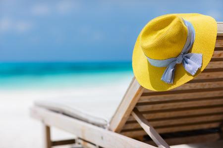 chapeau de paille: Chapeau jaune sur une chaise longue sur la plage tropicale