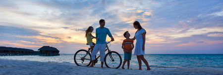 Familie met een fiets op tropisch strand bij zonsondergang Stockfoto
