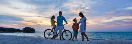 Familj med en cykel p� tropiska stranden i solnedg�ngen