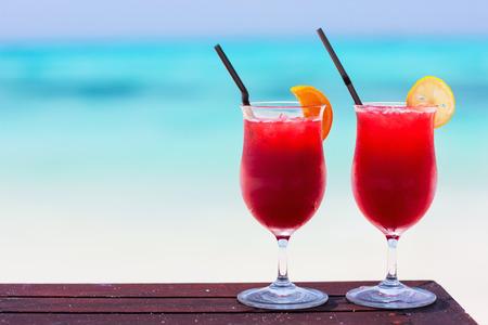 Två tropiska cocktails serveras på vacker strand
