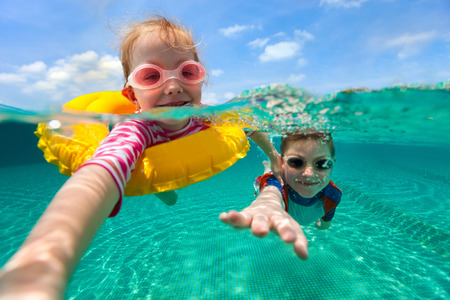 Split above and underwater photo of adorable kids having fun swimming on summer vacation