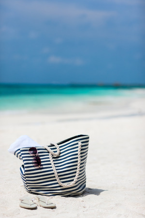 glasses in the sand: Bag with beach towel, sun glasses and flip flops on a tropical beach