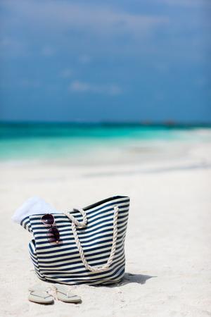 beach towel: Bag with beach towel, sun glasses and flip flops on a tropical beach