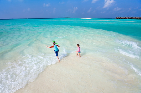 Above view of a stunning tropical ocean and white sand beach with kids plashing at shore photo