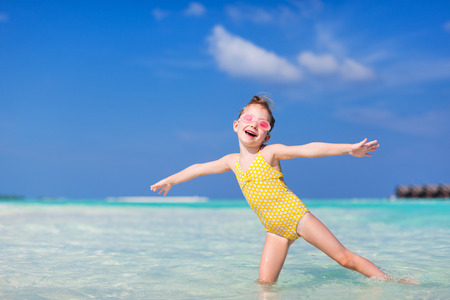 Adorable little girl splashing in tropical water during summer vacation Stock Photo