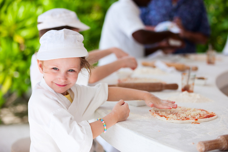 Adorable little girl dressed as a chef making pizza photo