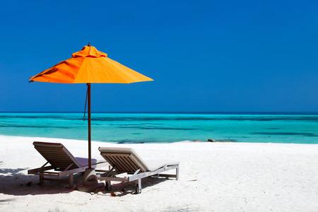 몰디브의 아름다운 열대 해변 의자와 오렌지 우산 스톡 콘텐츠