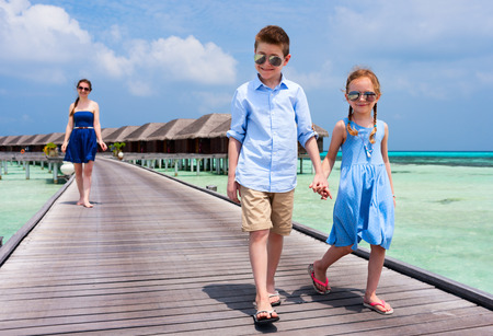 Cute little kids walking together on wooden jetty at tropical resort photo