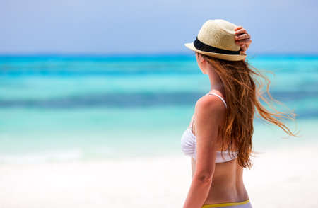 woman back view: Back view of a young beautiful woman in a straw hat at tropical beach