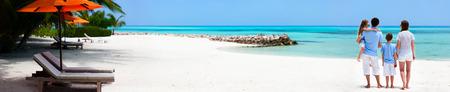 Bakifrån av en vacker familj på en strand under sommarsemester. Bred panorama, perfekt för banderoller
