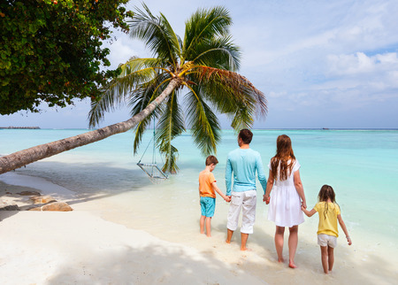 the maldives: Back view of a beautiful family standing on a tropical beach with palm tree during summer vacation