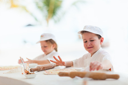 Adorable little girl and cute boy dressed as chefs making pizza photo