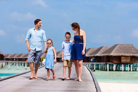 Happy beautiful family walking on wooden jetty during summer vacation at luxury resort photo