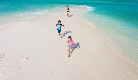 angle views: Above view of kids in a colorful sun protection swimwear running and having fun at beach
