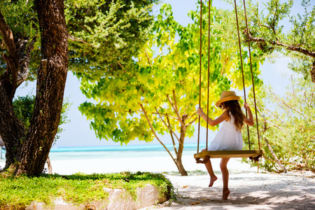 girl on swing: Back view of a little girl having fun on a swing on summer day  Stock Photo