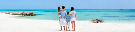 resort beach: Back view of a beautiful family on a beach during summer vacation. Wide panorama, perfect for banners Stock Photo