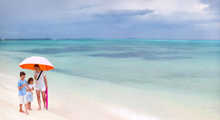Family walking with colorful orange umbrella on a white sand tropical beach at rainy day photo
