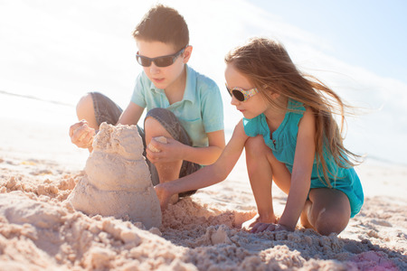 Brother and sister building sand castle at tropical beach Stock Photo