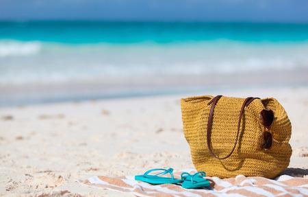 해변 휴가를 닫습니다. 밀짚 가방, 태양 안경, 수건 및 플립 열 대 해변에 퍼