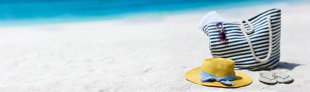 Stråhatt, väska, solglasögon och flip flops på en tropisk strand Stockfoto