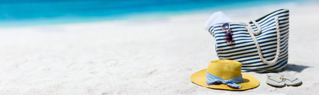 Straw hat, bag, sun glasses and flip flops on a tropical beach photo