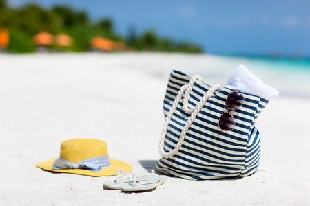 Cappello di paglia, borsa, occhiali da sole e infradito su una spiaggia tropicale