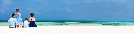 Bakifrån av en vacker familj på en strand under sommarsemester. Panorama perfekt för banderoller