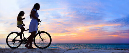 Panorama of mother and daughter with bike on a beach at sunset photo