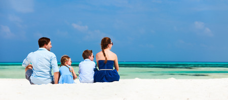 Back view of a beautiful family on a beach during summer vacation. Panorama perfect for banners Stockfoto