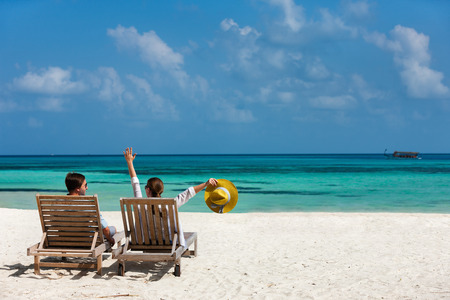 loungers: Back view of a couple relaxing on beach loungers during tropical vacation