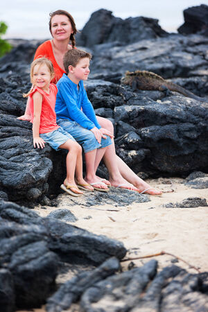 Mother and kids looking at endemic marine iguana while on vacation at Galapagos islands photo