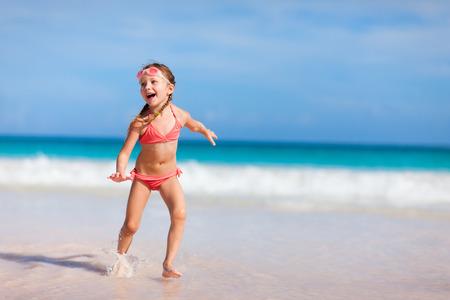 Adorable little girl having fun at beach on summer vacation photo