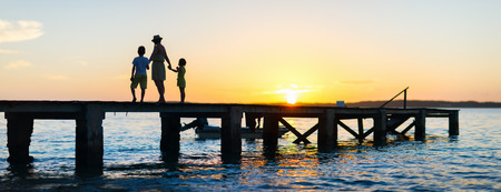 Family silhouettes on a bridge during sunset photo