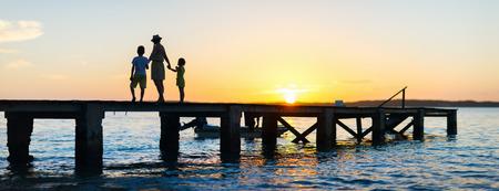 Silhouettes de famille sur un pont au coucher du soleil Banque d'images