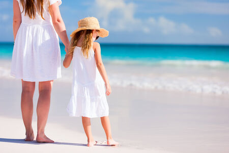 Back view of mother and daughter at Caribbean beach enjoying summer vacation photo